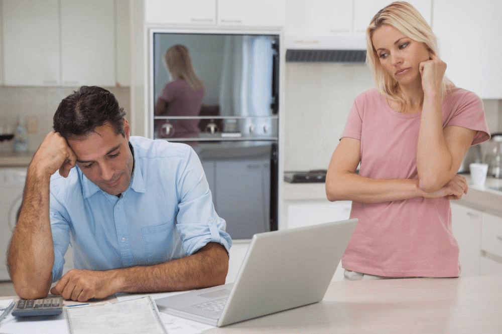 unhappy couple with bills and laptops in kitchen