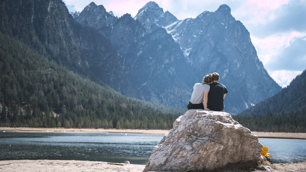 A couple cuddling on a rock in front of a lake