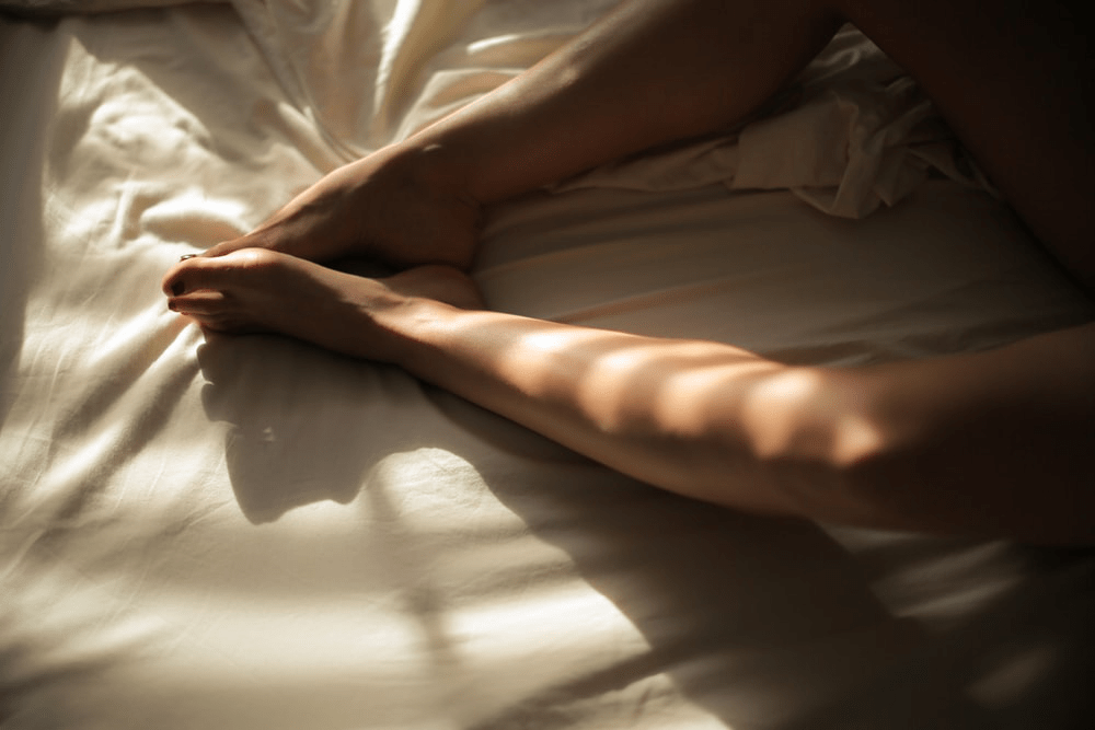 Sunlight falling on a pair of legs on a bed