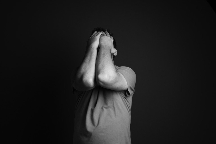 A person feeling anxious and covering his face