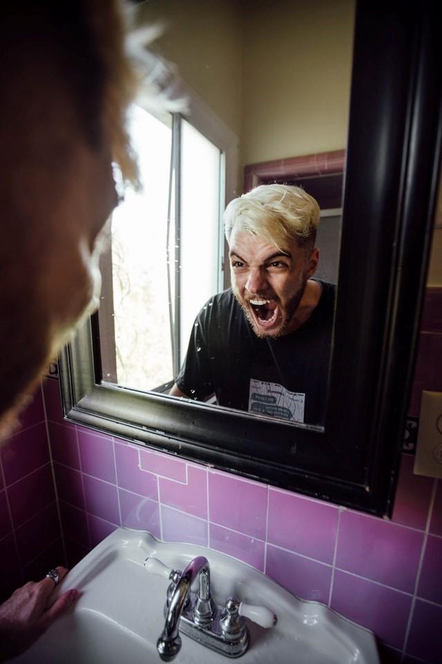 A man yells into a mirror