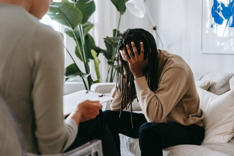 A man sits with his therapist, hiding face in shame, anxiety, and stress.