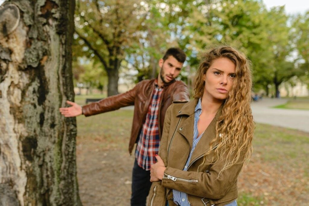 A couple has a public fight in the middle of a park, as the woman walks away.