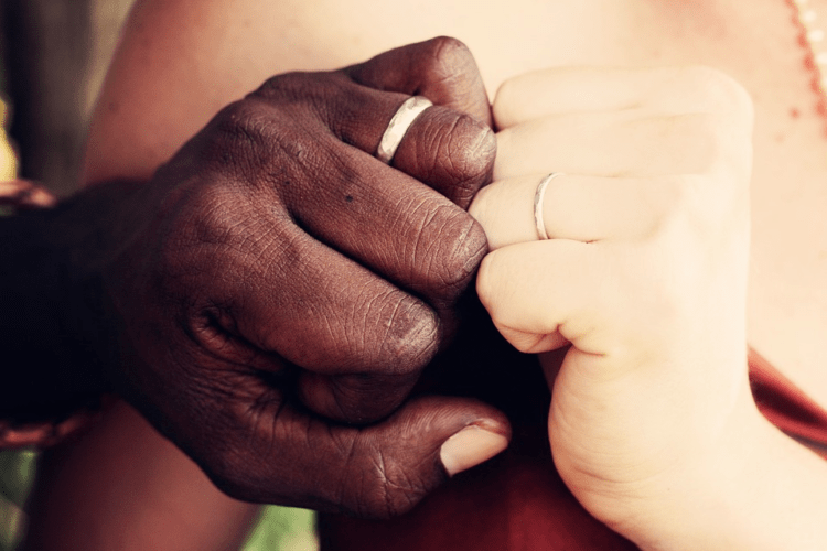 A cross-cultural couple showing their wedding bands