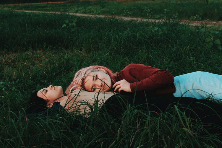 A same-sex couple laying in the field